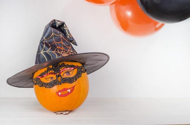Citrouille Avec Visage Peint En Chapeau De Sorcière Près De Ballons Orange Et Noirs Photo Premium