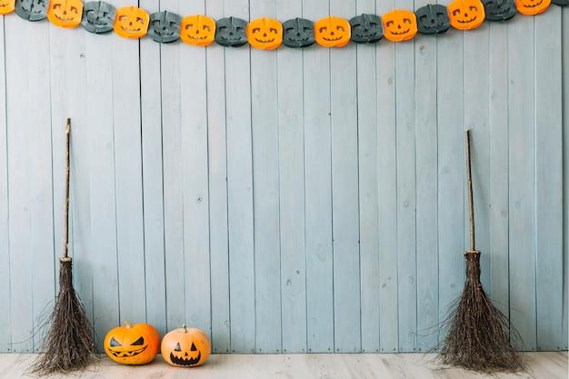 Citrouilles Et Balais Près Du Mur Avec Décoration D'halloween Photo gratuit