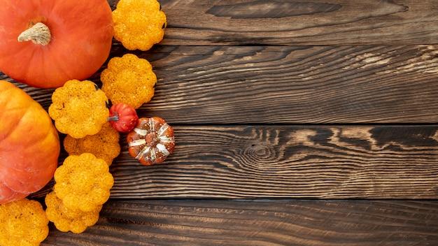 Citrouilles colorées plates sur fond en bois Photo gratuit