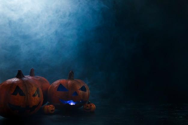 Citrouilles décoratives d'halloween avec éclairage intérieur et fumée Photo gratuit