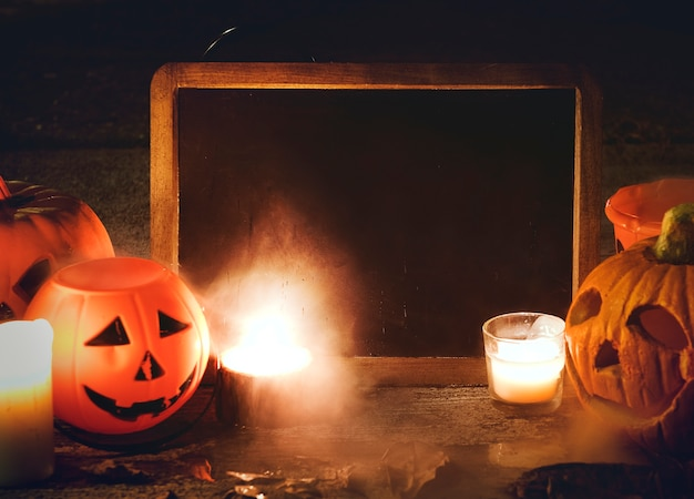 Citrouilles d'halloween et bougies avec tableau noir Photo gratuit