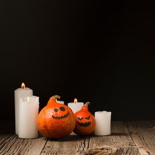Citrouilles d'halloween et bougies vue de face Photo gratuit