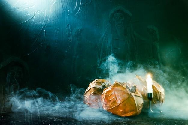 Citrouilles d'halloween faites à la main avec bougie allumée et fantôme et fumée Photo gratuit