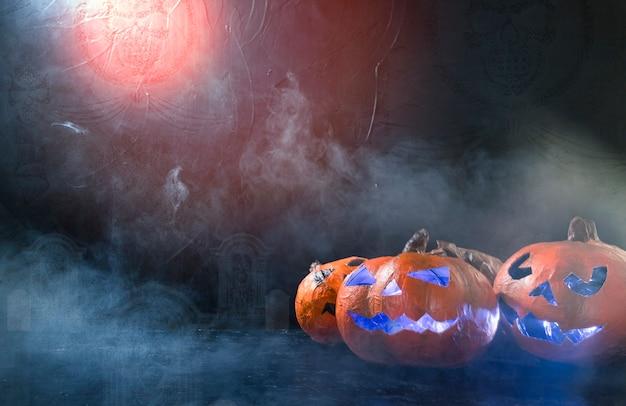 Des citrouilles à la main d'halloween illuminées à l'intérieur de la fumée Photo gratuit