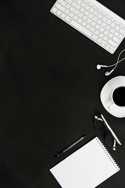 Clavier blanc; écouteur; tasse à café; lunettes; stylo et bloc-notes en spirale contre un bureau noir Photo gratuit