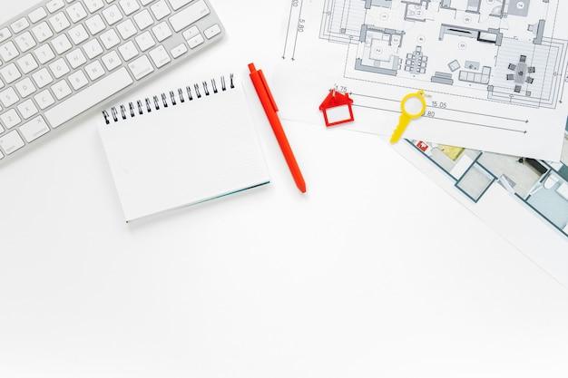 Clavier; laiterie en spirale et blueprint sur le bureau blanc Photo gratuit