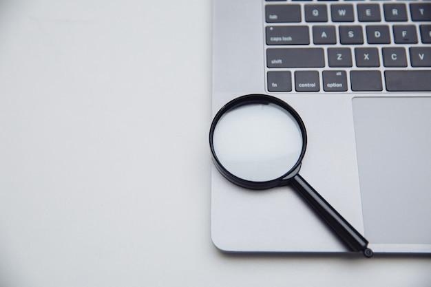 Clavier D'ordinateur Portable Avec Loupe. Concept De Recherche. Photo Premium