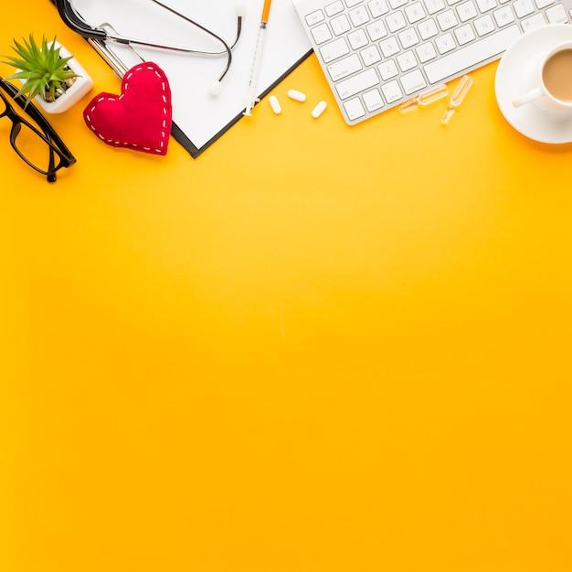 Clavier; presse-papiers; en forme de cœur cousu; médicament; injection; lunettes et stéthoscope; tasse de thé disposée sur la surface jaune Photo gratuit