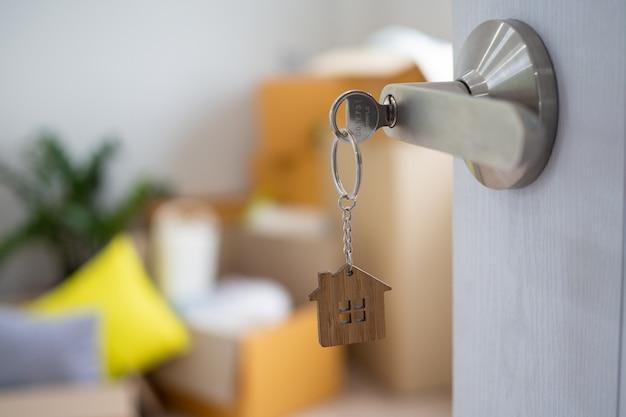 La clé de la maison pour déverrouiller une nouvelle maison est branchée à la porte. Photo Premium