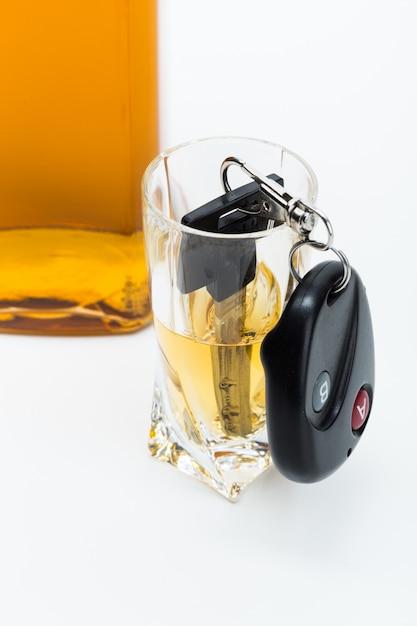 Clé de voiture sur le bar avec de l'alcool renversé Photo Premium