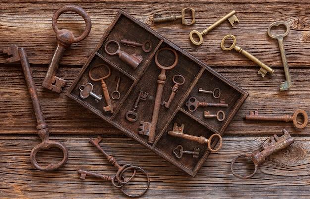 Clés anciennes dans un coffret en bois sur un fond en bois vintage. Photo Premium