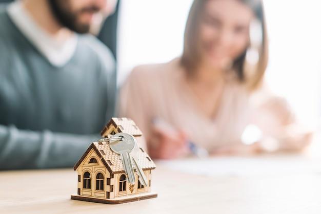 Clés et petite maison près de couple floue Photo gratuit