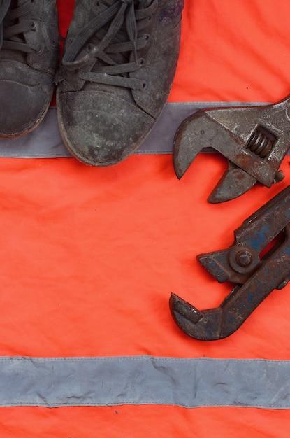 Des clés réglables et de vieilles bottes reposent sur une chemise orange de signaleur Photo Premium