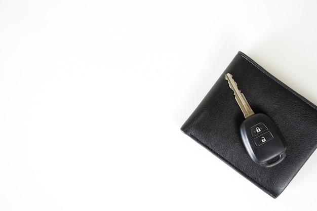 Clés de voiture sur le portefeuille isolé sur blanc avec un espace sur la gauche. Photo Premium