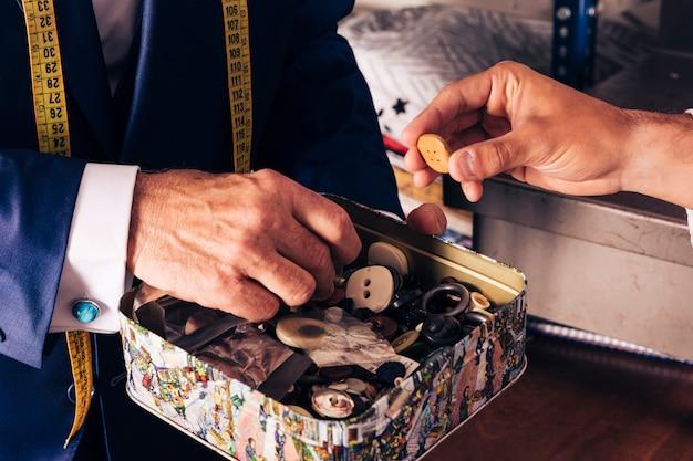 Client masculin sélectionnant un bouton dans le conteneur en attente du couturier Photo gratuit