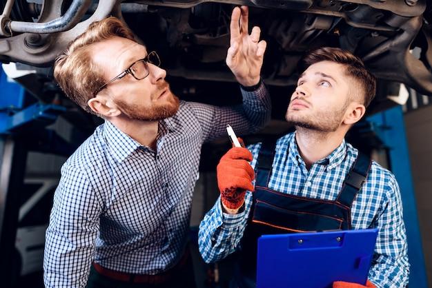 Client et mécanicien vérifient les détails de la voiture. Photo Premium