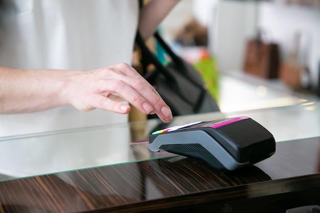 Client Payant Son Achat Par Carte De Crédit Dans Un Magasin De Vêtements, En Entrant Le Code Pin. Photo Recadrée, Gros Plan Des Mains. Concept D'achat Ou D'achat Photo gratuit