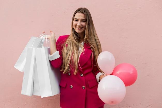 Client Portant Des Vêtements De Mode Et Tenant Des Ballons Coup Moyen Photo gratuit