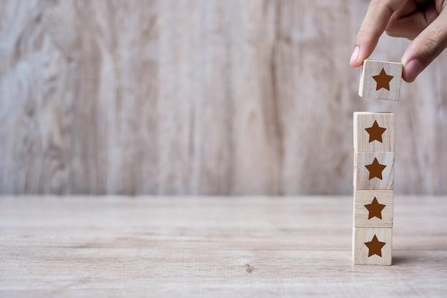Client tenant des blocs de bois avec le symbole cinq étoiles Photo Premium