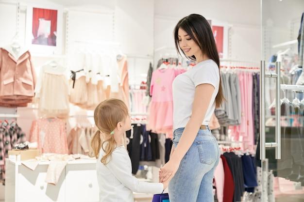 Clients Choisissant Des Vêtements élégants Pour Enfants En Boutique. Photo gratuit