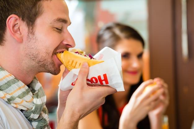 Des clients mangeant du hotdog dans un snack rapide Photo Premium