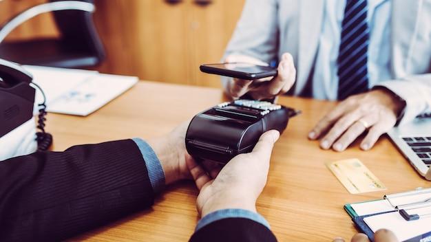 Les clients qui paient leurs factures rapidement grâce à la technologie de paiement nfc avec application mobile dans un smartphone. Photo Premium