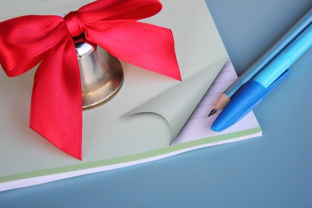 Une cloche en métal avec un arc rouge est située sur le cahier d'école à côté du stylo et du crayon. Photo Premium