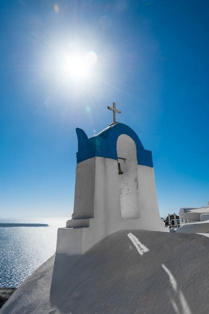 Clocher blanc et bleu avec soleil à santorin Photo Premium