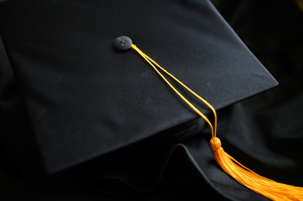 Close-up black graduation hat et yellow gass placé sur le sol Photo Premium