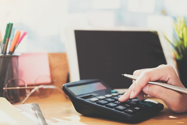 Close Up Business Woman Using Calculator And Laptop For Do Math Finance On Desk In Wooden Desk In Office And Business Working Background, Tax, Accounting, Statistics And Analytic Research Concept Photo Premium