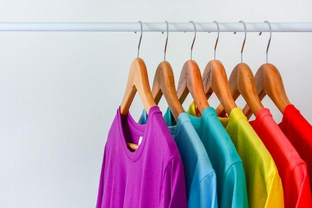 Close up collection de t-shirts arc-en-ciel coloré accroché sur un cintre en bois dans le placard Photo Premium
