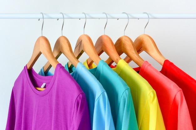 Close up collection de t-shirts colorés arc-en-ciel suspendus sur un cintre en bois dans un placard ou un porte-vêtements Photo Premium