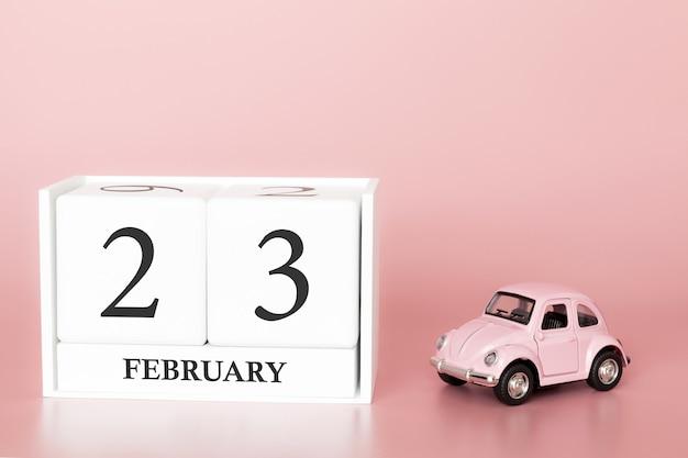 Close-up cube de bois le 23 février. jour 23 du mois de février, calendrier rose avec voiture rétro. Photo Premium
