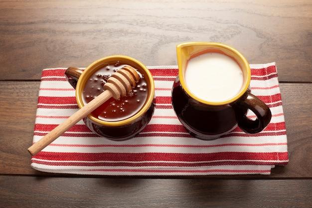 Close-up cups avec du miel et du lait Photo gratuit