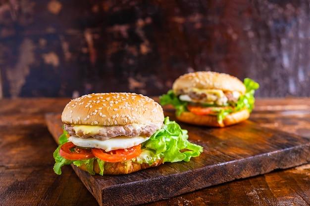 Close-up de délicieux burger fait maison avec de la laitue, du fromage, des oignons et des tomates sur une planche de bois rustique sur une table en bois Photo Premium