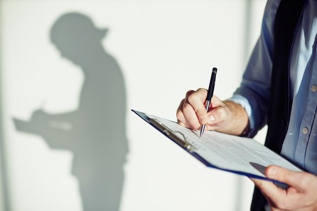 Close-up de l'écriture des employés sur un presse-papiers Photo gratuit