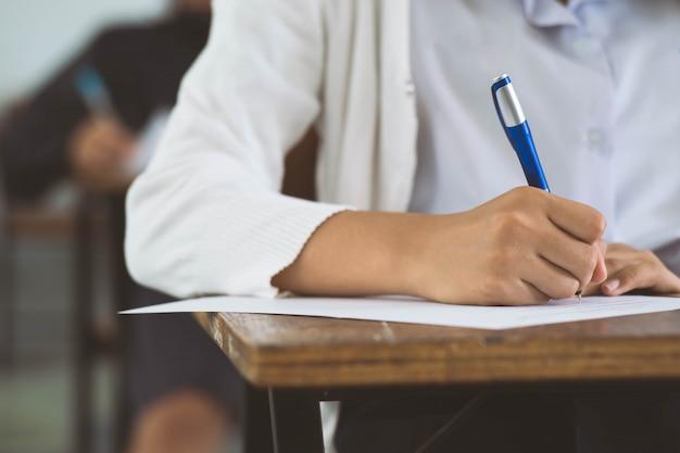 Close up les élèves qui écrivent et lisent les feuilles de réponses aux examens en classe d'école avec stress. Photo Premium