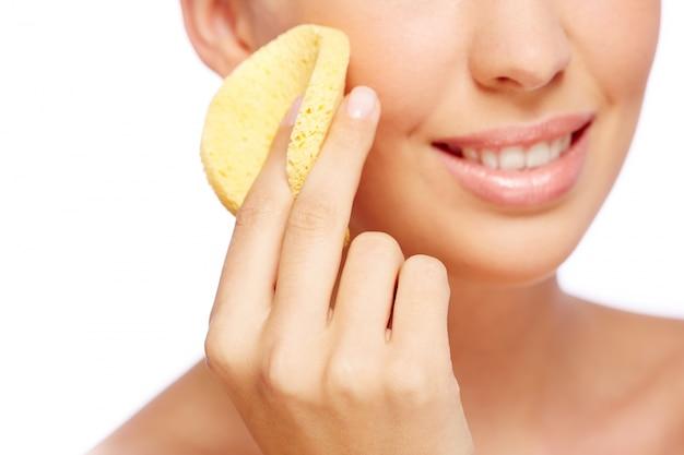 Close-up d'une femme à l'aide d'une éponge dans son visage Photo gratuit