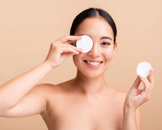 Close-up femme asiatique avec des tampons de coton Photo gratuit