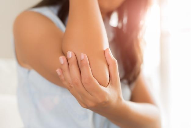 Close up femme ayant la douleur au coude blessé. concept de soins de santé et douleur au bras. Photo Premium