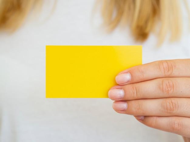 Close-up femme brandissant une carte de visite jaune Photo gratuit
