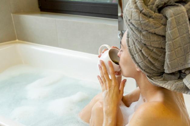 Close-up femme buvant du café dans la baignoire Photo gratuit
