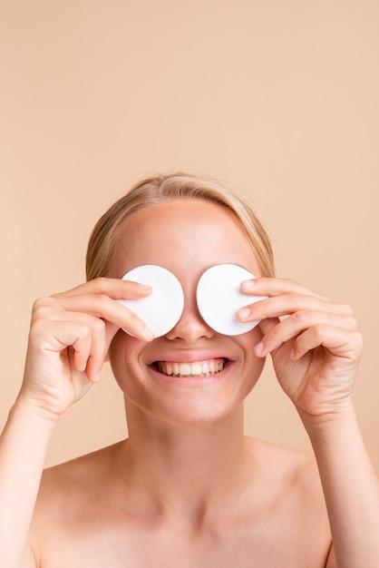Close-up femme couvrant ses yeux avec des tampons de coton Photo gratuit