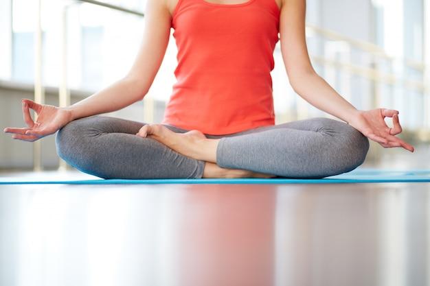 Close-up de la femme à méditer dans la salle de gym Photo gratuit
