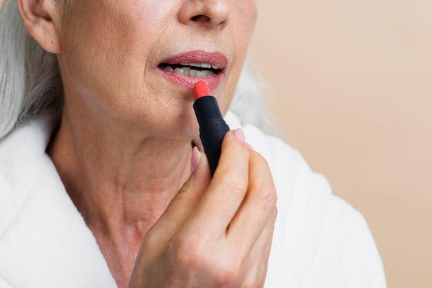 Close-up femme mûre appliquer du rouge à lèvres Photo gratuit