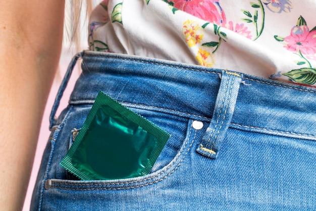 Close-up femme avec préservatif enveloppé dans sa poche Photo gratuit