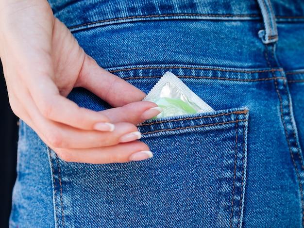 Close-up femme avec préservatif vert dans la poche arrière Photo gratuit