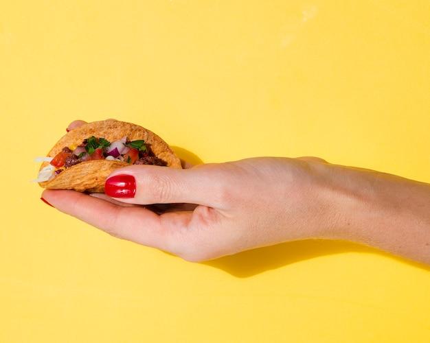 Close-up femme tenant un taco avec fond jaune Photo gratuit