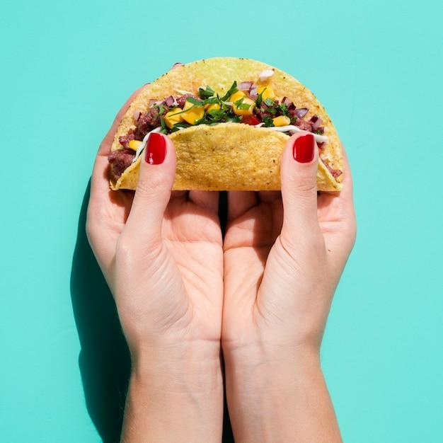 Close-up femme tenant taco avec fond vert Photo gratuit