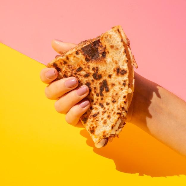 Close-up femme tenant une tortilla avec un fond coloré Photo gratuit